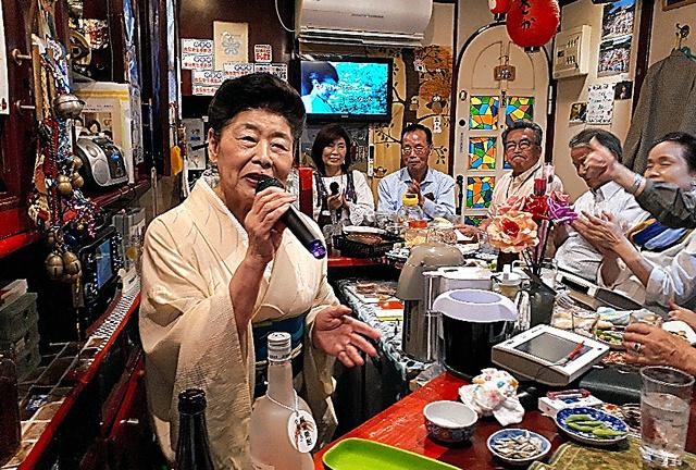 カウンターの客に囲まれ歌う「年金バーさかえ」ママの光武栄子さん=福岡市中央区今泉1丁目