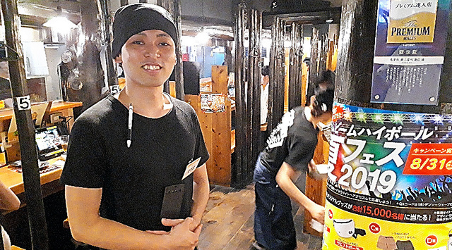 「鳥貴族 錦三袋町通店」の相馬未来店長。奥に半個室の客席が続く=名古屋市中区錦3丁目