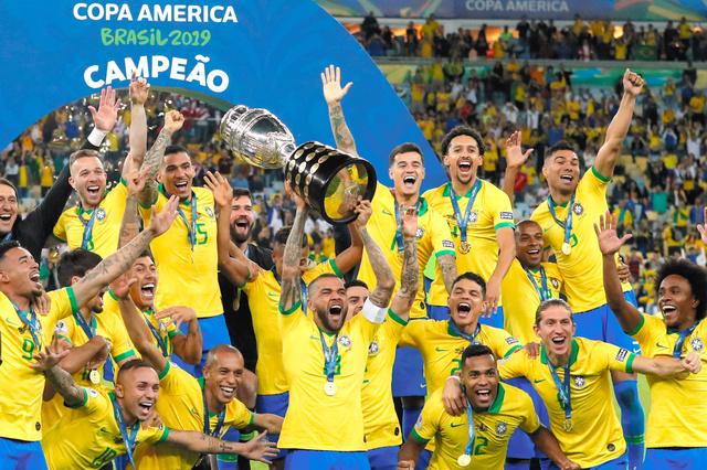 優勝トロフィーを掲げるブラジルのアウベスと、喜ぶ選手たち=AP
