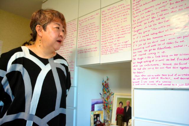 自宅の壁に貼った英文で語り部の練習をする高橋匡美さん。棚には両親の遺影がある=宮城県塩釜市