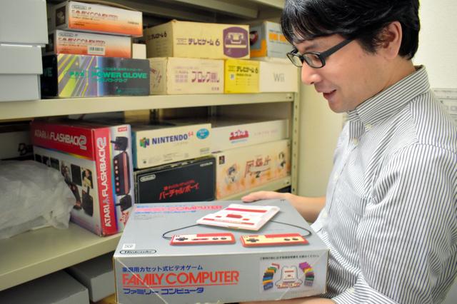 保管しているファミコンを持つ立命館大の井上明人講師=京都市