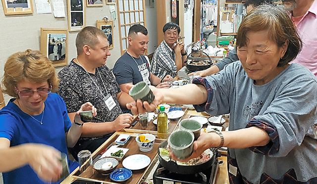 ウクライナから訪れた客に食事を出す小林友子さん=6月、福島県南相馬市の「双葉屋旅館」