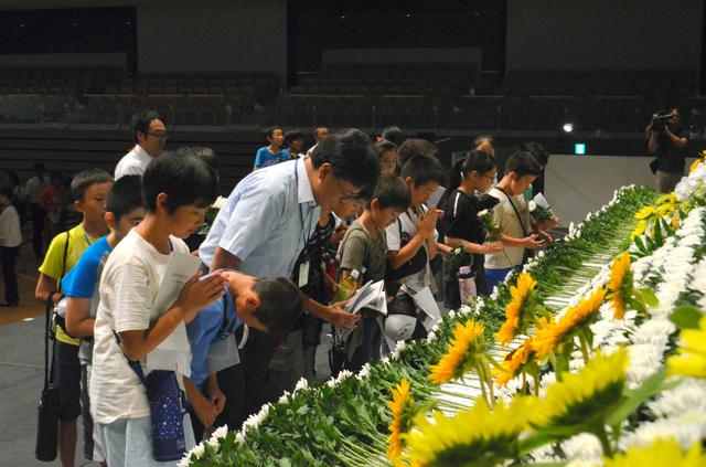 長岡空襲の犠牲者に花を手向ける平和祈念式典の参加者たち=1日、アオーレ長岡