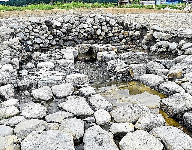 飛鳥京跡苑池で出土した石組みの溝。写真奥の正方形の枡の地下から水がわき、溝に流れる=6日、代表撮影