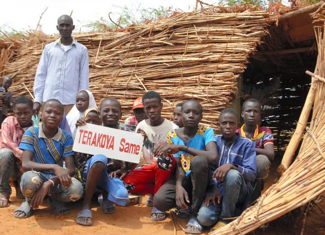 今年は14人が寺子屋で学んでいる。後ろが村人が総出で作るかやぶきの教室。イブラヒム・ガド先生(左後ろ)は「公教育に戻れるように教えている」と話す=2019年6月29日、ニジェール・クオラテギ村、大久保真紀撮影