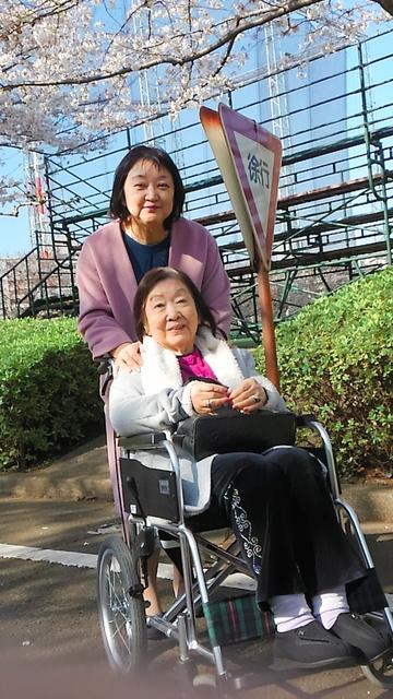 2018年3月、車いすに乗った母親の玲子さんと、自宅近くの桜並木を散歩する松岡ルミさん(本人提供)