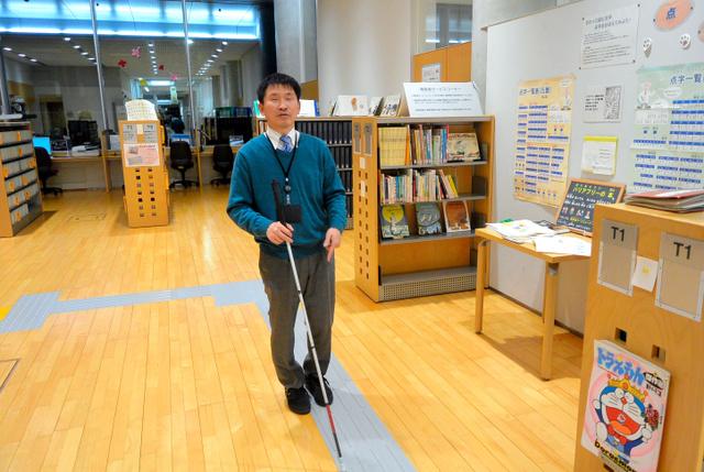 職場で白杖を使って歩く大川和彦さん=千葉市中央区