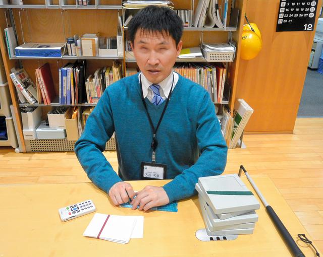 点字を使って録音図書の貸し出し作業をする大川和彦さん=千葉市中央区