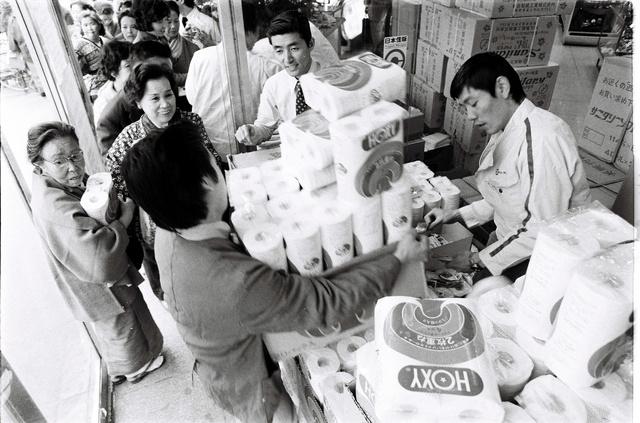 山のように積み上げられたトイレットペーパーを行列して買い求める人たち=1973年11月、東京都北区