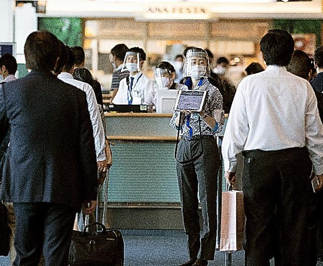 羽田空港の搭乗口前で、空港係員がフェースシールドをつけて案内していた=4日、長島一浩撮影