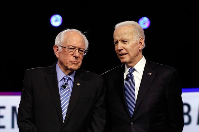 今年2月のテレビ討論会を前に言葉を交わす、バイデン前米副大統領(右)とサンダース上院議員=AP