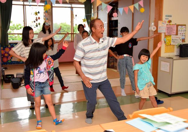 しまくとぅばで沖縄民謡を歌いながら踊る玉城弘さん(中央)と子どもたち=沖縄県浦添市