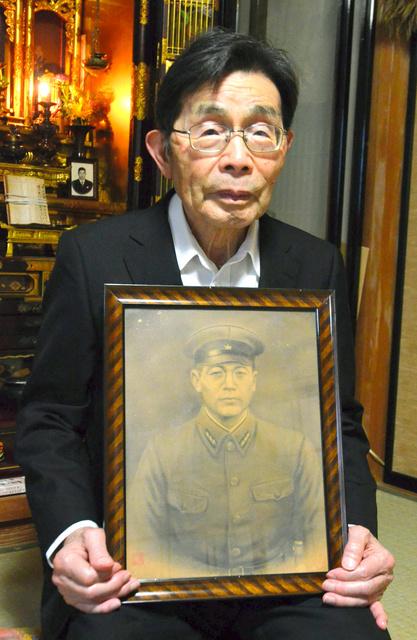 祖父・源治の遺影を持つ私の父(源治の三男)。5月に亡くなった叔父の法要にきた。生前の祖父を知る唯一の肉親だ=新潟県長岡市