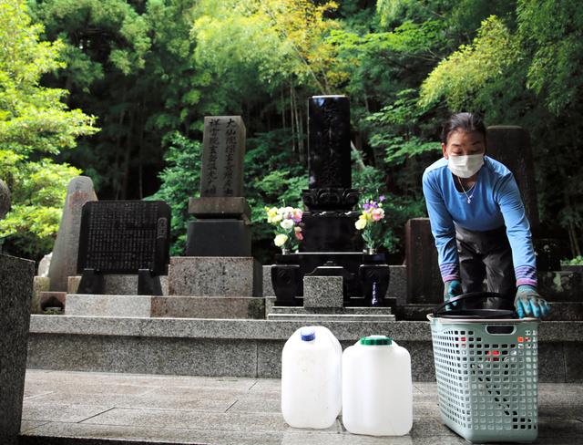 お墓の掃除をする佐々木やす子さん=福島県浪江町津島地区、三浦英之撮影