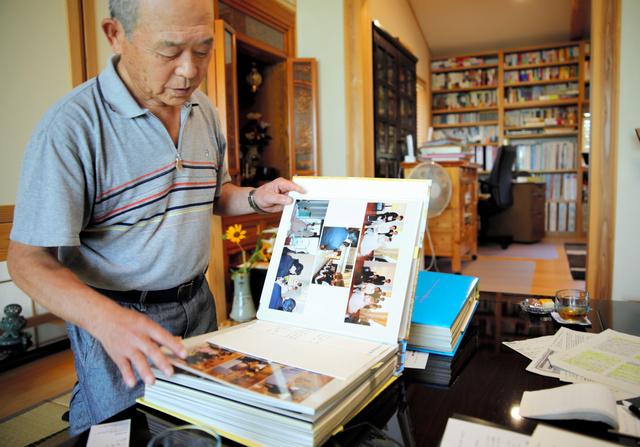 自宅から持ち出したアルバムを見つめる今野秀則さん=2020年8月、福島県大玉村大山、三浦英之撮影