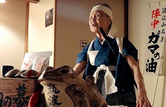 夜の宴席でガマ口上を披露する吉岡久子さん。よどみなく流れる口上に客は聞きほれた=2013年