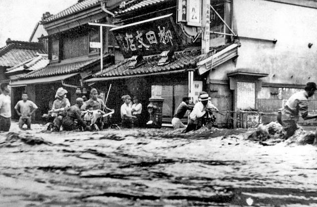 激しい流れの中、綱を頼りに歩く人々(栃木県足利市通2丁目、国交省渡良瀬川河川事務所提供)