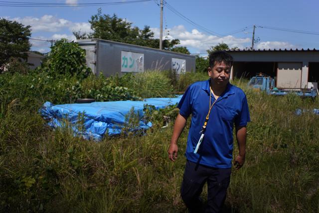 ブルーシートにくるまれて置かれている「原子力広報塔」を見に訪れた大沼勇治さん=2020年8月28日午前、福島県双葉町、小玉重隆撮影