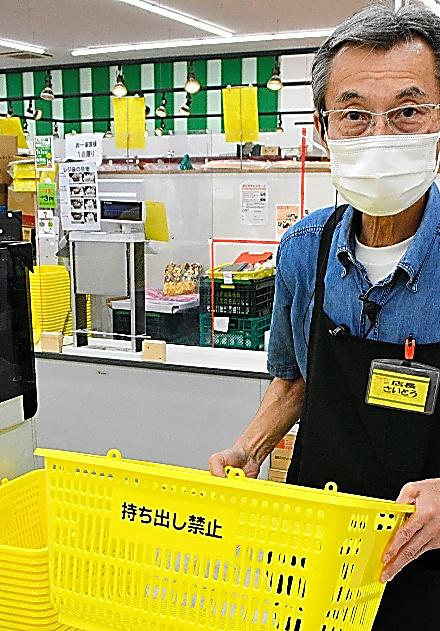 「カゴパク」の被害に遭っているカゴを手にする斎藤店長=いずれもスーパー「マルサン吉川店」