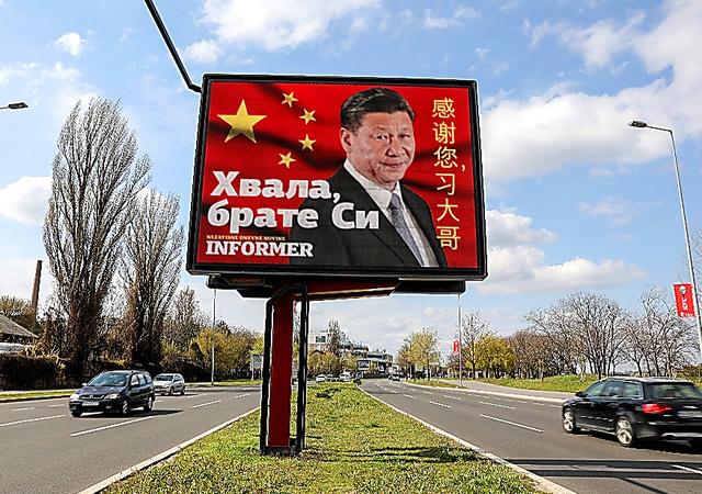 新型コロナウイルスの感染が拡大する中、中国の国家主席、習近平が描かれた看板のそばを車が走る。看板には「ありがとう、習兄さん」と書かれている=4月1日、セルビア・ベオグラード、ロイター