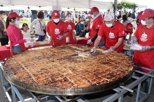 取り分けられる直径2メートルのアップルパイ=2020年9月27日午前11時27分、弘前市りんご公園、林義則撮影