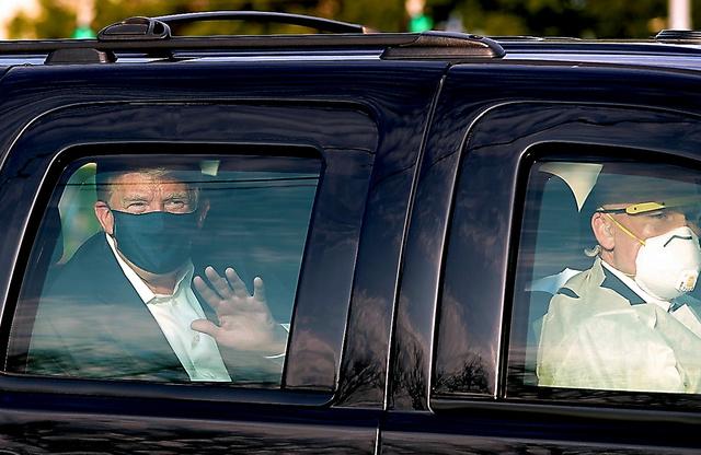 4日、米メリーランド州の病院前に集まった支持者に手を振るトランプ米大統領=AFP時事。車は密閉されており、同乗者の感染リスクが指摘されている