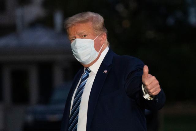 ワシントンで5日、退院してホワイトハウスに戻る際に親指を立ててみせるトランプ大統領=AP