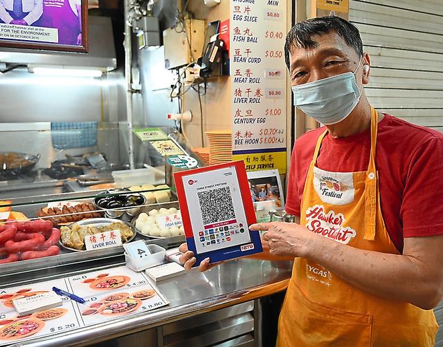 屋台街「マックスウェル・フードセンター」で、決済用のQRコードを説明するウン・コクファさん=9月25日、シンガポール、西村宏治撮影