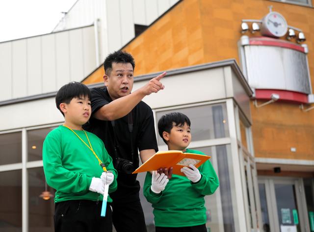 JR双葉駅前から町の状況を説明する大沼勇治さん(中央)と勇誠くん(左)、勇勝くん=2020年9月、福島県双葉町、三浦英之撮影