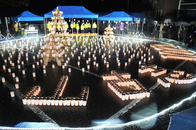 追悼式典の会場では、キャンドルが「山古志」の文字を浮かび上がらせた=2020年10月23日夜、新潟県長岡市山古志竹沢、高橋俊成撮影
