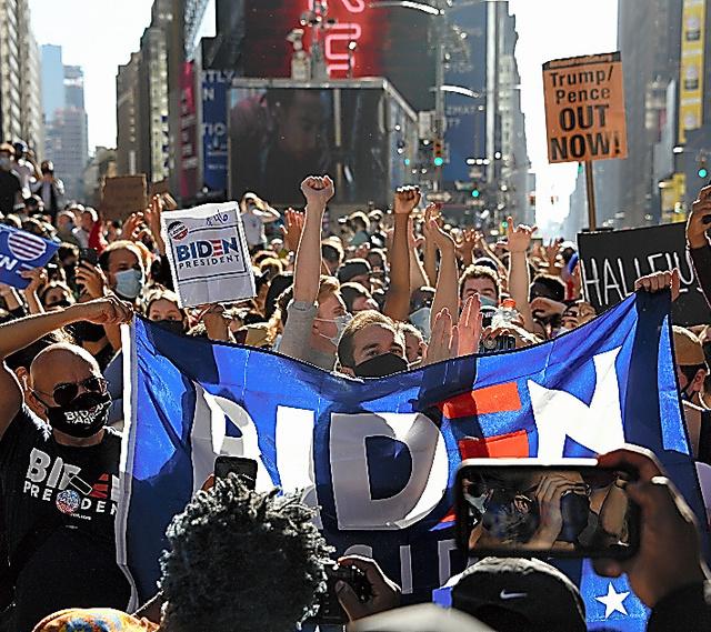観光名所のタイムズスクエアに集まり、バイデン氏の当選を喜ぶ人たち=7日午後1時34分、ニューヨーク、鵜飼啓撮影