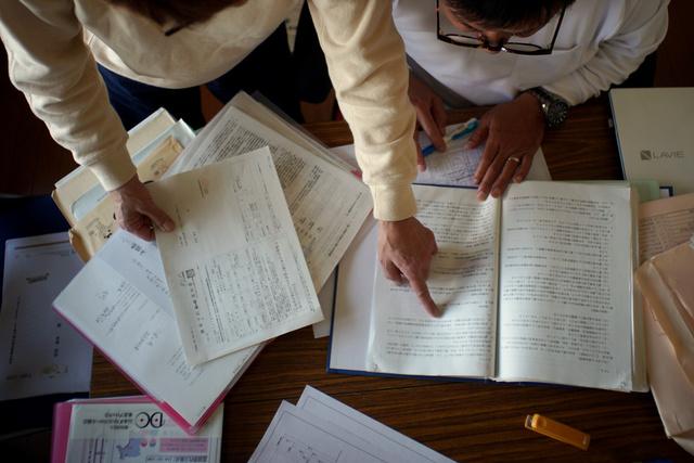住宅ローンの書類や再建した自宅の図面を見る長沼俊幸さん(右)、美雪さん夫婦=宮城県名取市閖上、小玉重隆撮影