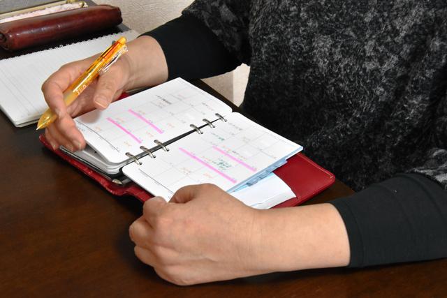 女性のスケジュール帳を手に語る京都府に住む派遣社員の女性。11月はようやく仕事の予定が10日ほど入った=2020年10月30日、京都府内、遠藤隆史撮影