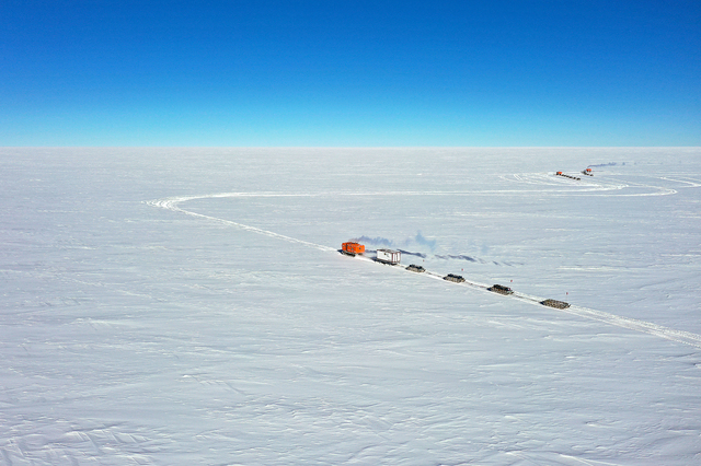 みずほ基地へ向かい、360度白い氷原を行く雪上車。計約20トンのそり列をひいてゆっくり走る=10月9日、南極大陸・内陸、ドローンで撮影