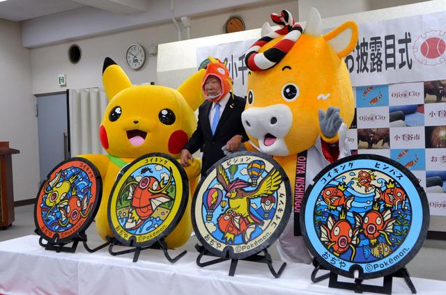 新潟県小千谷市内に4枚の「ポケふた」が設置されることになり、大塚昇一市長(中央)は「コイキング」のかぶり物でPR。ピカチュウも登場した=26日、小千谷市役所