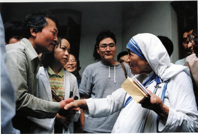 マザー・テレサ(右)と握手する森元美代治さん=1996年、インド・カルカッタ(現コルカタ)、八重樫信之さん撮影