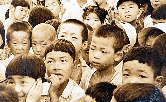 近所の寺の境内では、紙芝居もあった。前列左から2人目、爪をかんでいるのが古谷敏さん=本人提供
