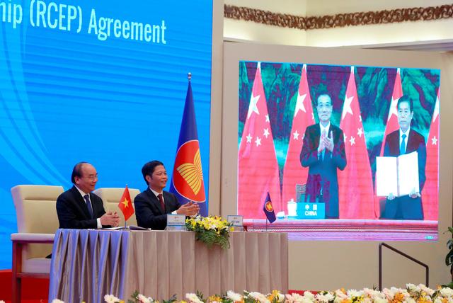 地域的包括的経済連携(RCEP)の署名式で、拍手するベトナムのフック首相(左)と、スクリーンに映る中国の李克強首相(右から2人目)ら=15日、AP