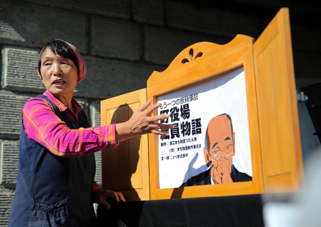 震災直後の状況を紙芝居で伝える石井さん=2020年10月、福島市、三浦英之