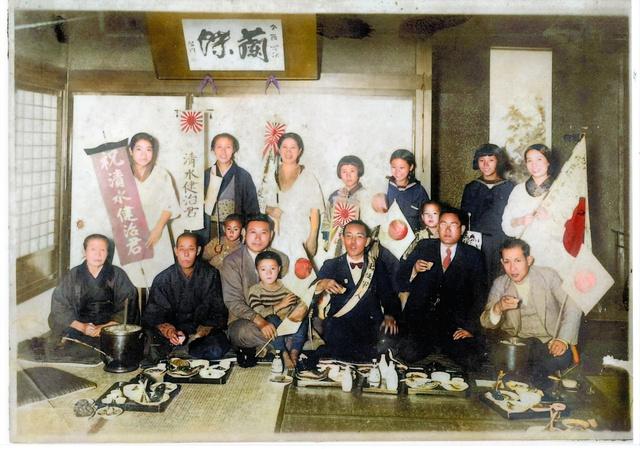 清水誠一さん(88)の父・健治さん(手前右から3人目)の日中戦争出征祝いに親族や父の友人が集まった。隣の男性のひざに座るのが誠一さん=1937(昭和12)年(提供:清水誠一さん・「空襲から復興へ」写真カラー化プロジェクト)