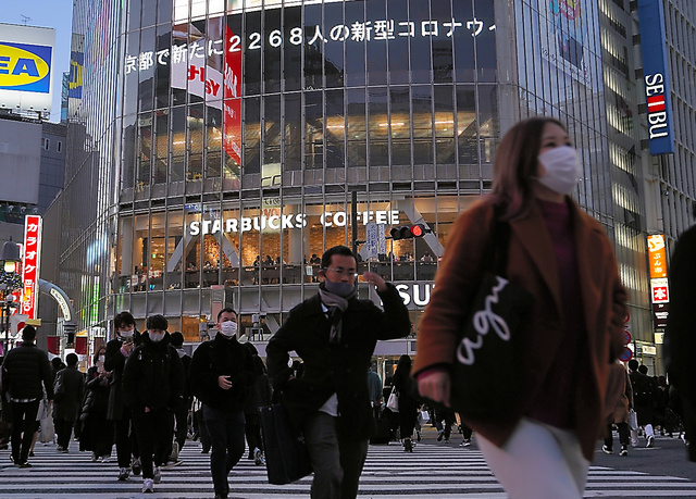 多くの人が行き交う渋谷スクランブル交差点。大型ビジョンには、東京都の新規感染者が3日連続で2千人を超えたことを伝えるニュースが流れていた=9日、東京都渋谷区、藤原伸雄撮影