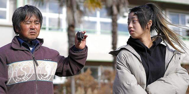 かつて通った熊町小学校で震災当時を振り返る木村舞雪さん(右)と、動画で記録する父の紀夫さん=6日、福島県大熊町