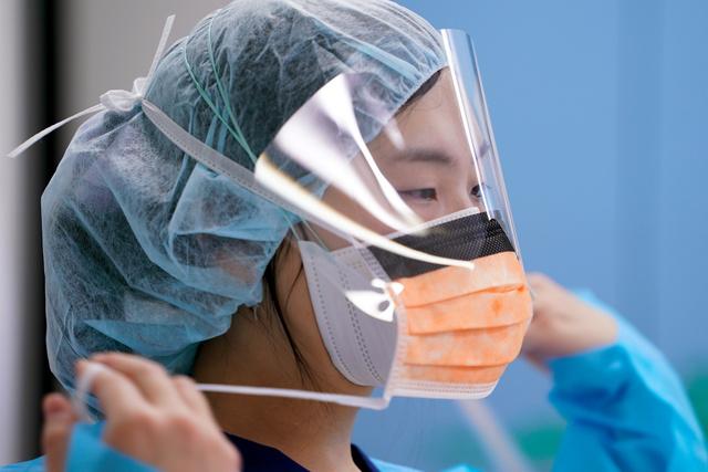 救急患者の受け入れに備え、研修医がマスクのひもを結んだ=2020年12月30日午後5時28分、東京都三鷹市の杏林大病院、加藤諒撮影