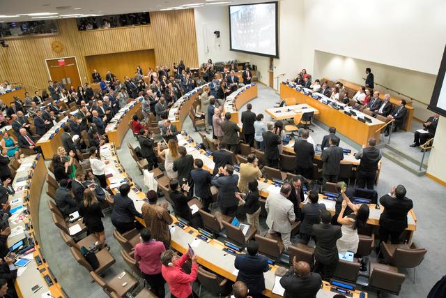 ニューヨークの国連本部で、核兵器禁止条約が採択され、立ち上がって拍手する各国の代表ら=2017年7月7日、AP