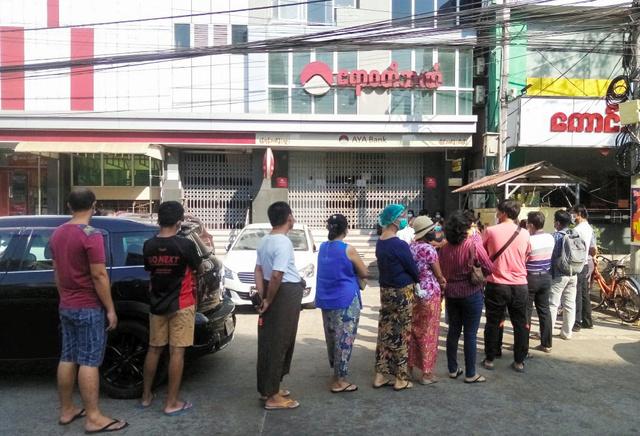 ヤンゴンで1日、銀行の支店に列をつくる人々=ロイター