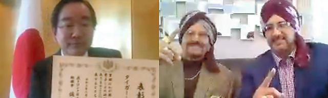 オンラインで佐々山拓也在トロント総領事(左)から表彰を受けたタイガー・ジェット・シン氏(中央)と息子のタイガー・アリ・シン氏=在トロント日本総領事館提供