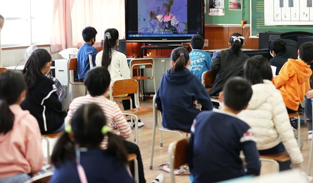 ビデオで音楽を鑑賞する児童たち。座席の間隔は1メートルあけてある=2021年2月17日、横浜市南区の日枝小、嶋田達也撮影