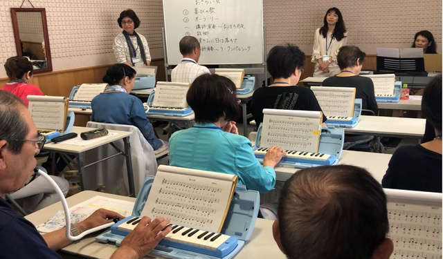 講師の指導を受けながら、鍵盤ハーモニカの練習をする人たち=積山薫教授提供