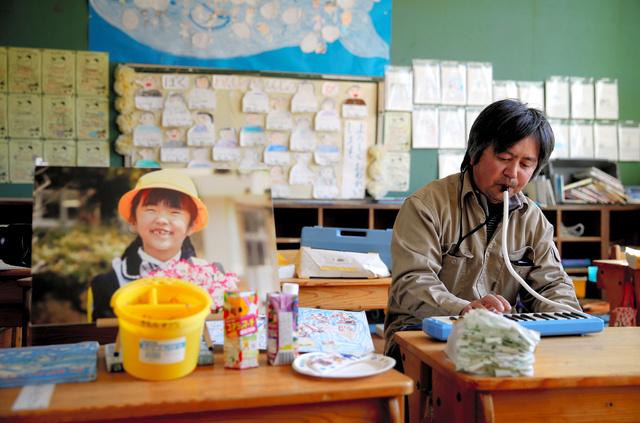次女の汐凪さんが通った熊町小学校の教室に写真を飾り、鍵盤ハーモニカを演奏する木村紀夫さん=2019年2月16日、福島県大熊町、三浦英之撮影