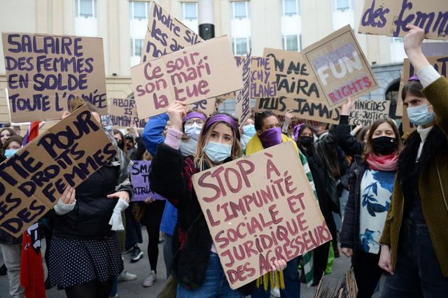 ベルギーのブリュッセルで8日、国際女性デーに合わせ、男女平等や女性への暴力根絶を求めてプラカードを掲げる女性たち=ロイター
